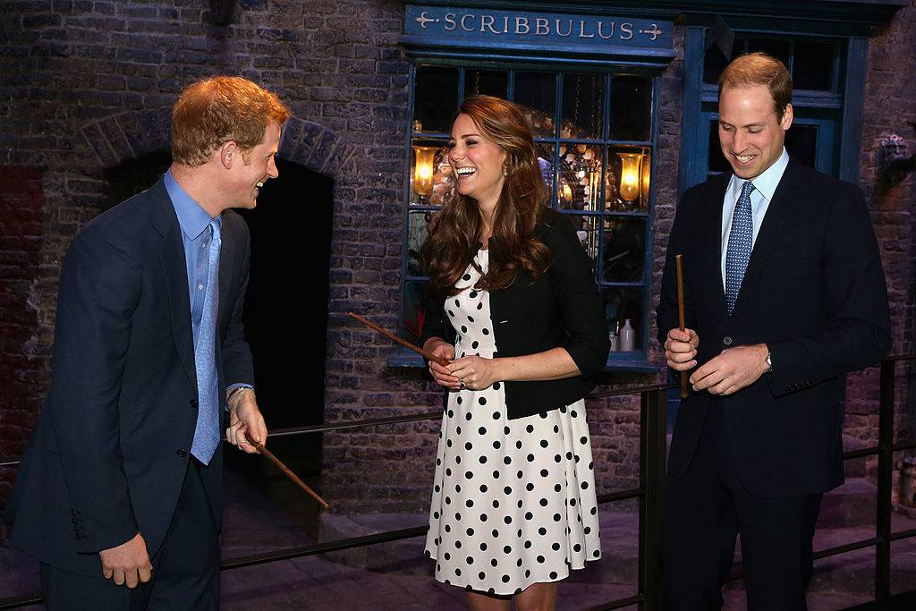 Prince Harry, Catherine, Duchess of Cambridge and Prince William, Duke of Cambridge laugh as they hold wands on the Harry Potter set