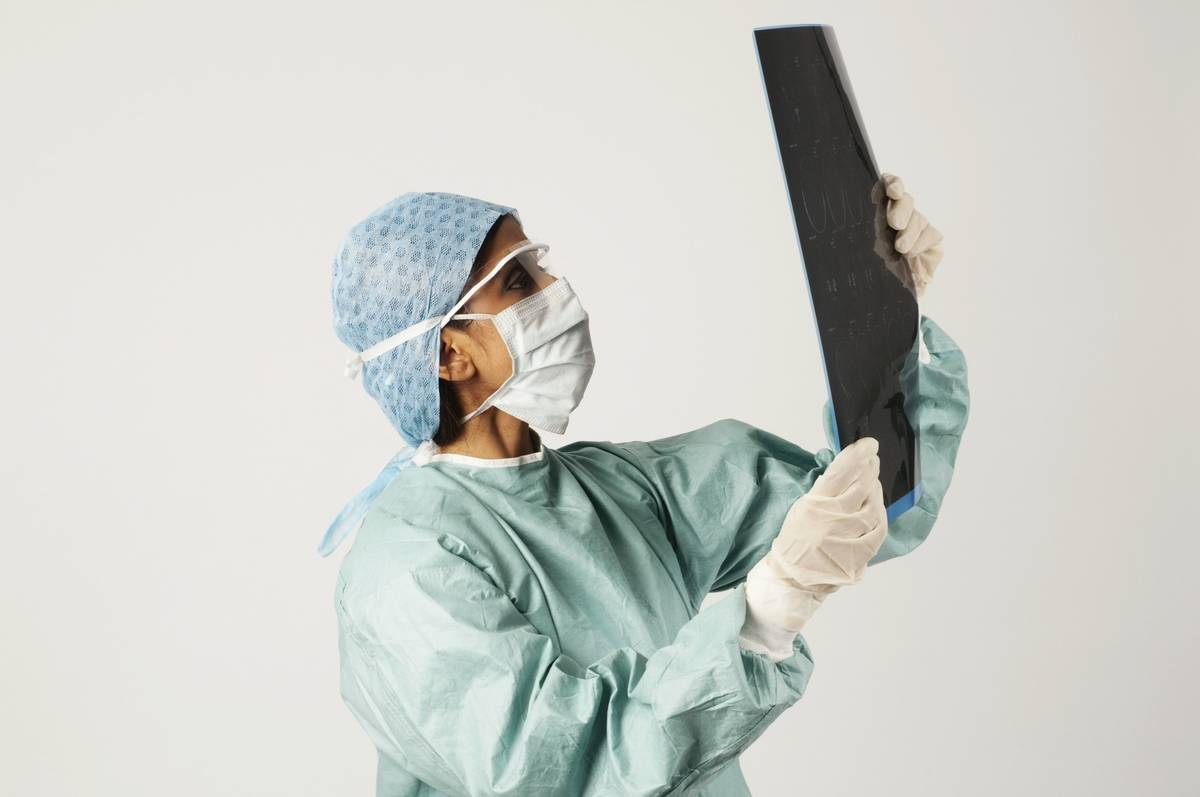 A surgeon examines a set of x-rays.