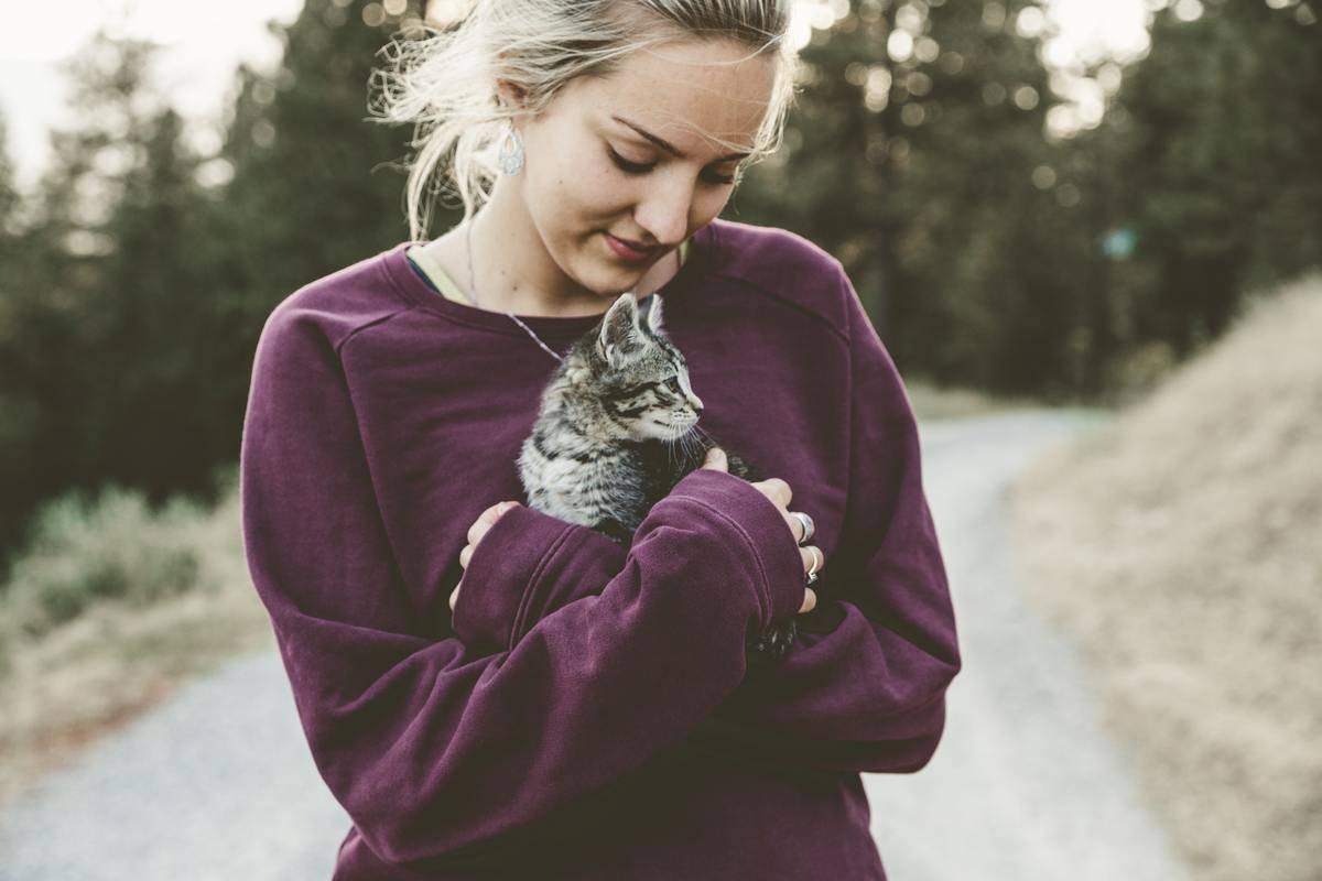 A woman holds a kitten.