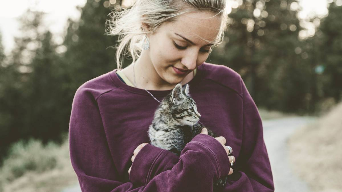A woman holds a cat.