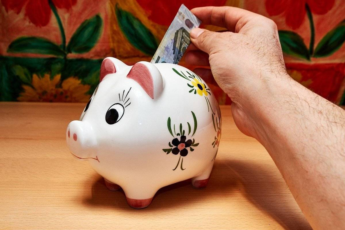 Someone puts cash in a piggy bank.