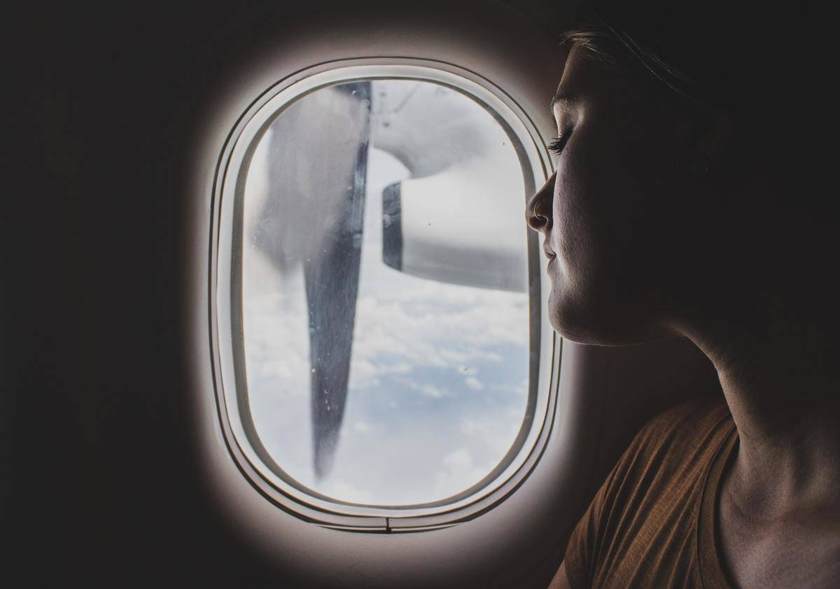 A woman looks out a plane window.