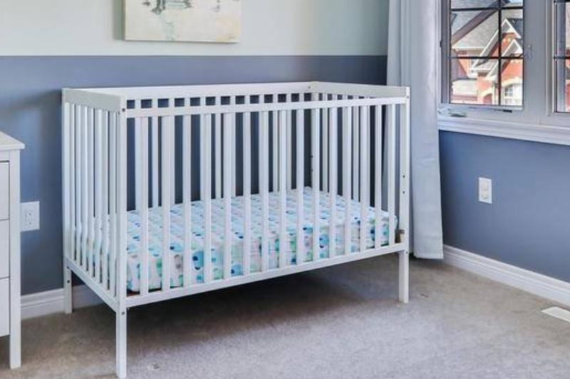 A white crib is seen in a baby boy's room.