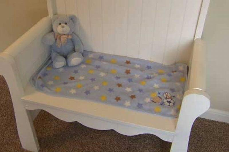 The bench made from the crib has a baby blanket and blue teddy bear.
