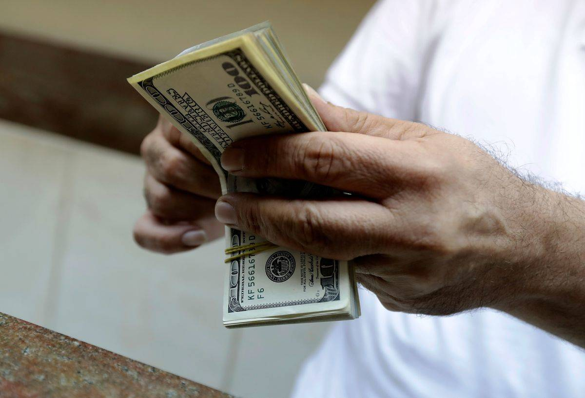A person holds several $100 bills.