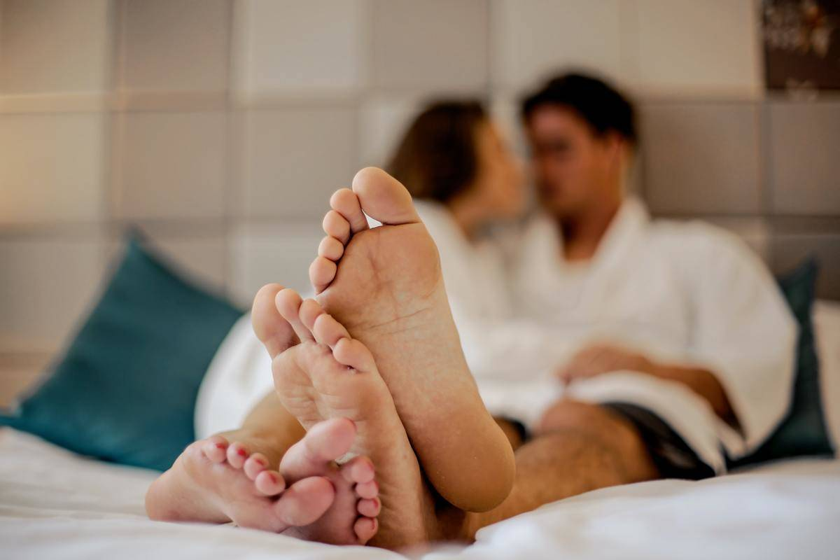 Couple wearing white robes relaxing in bed, focus on bottom of bare feet.