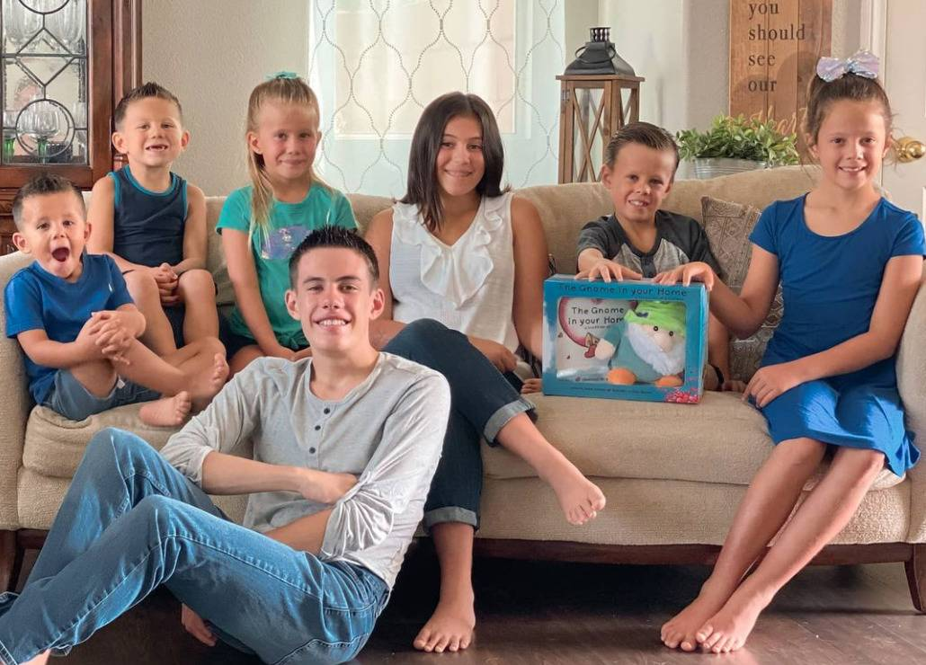 Seven kids up for adoption are pictured sitting on a couch with a toy.