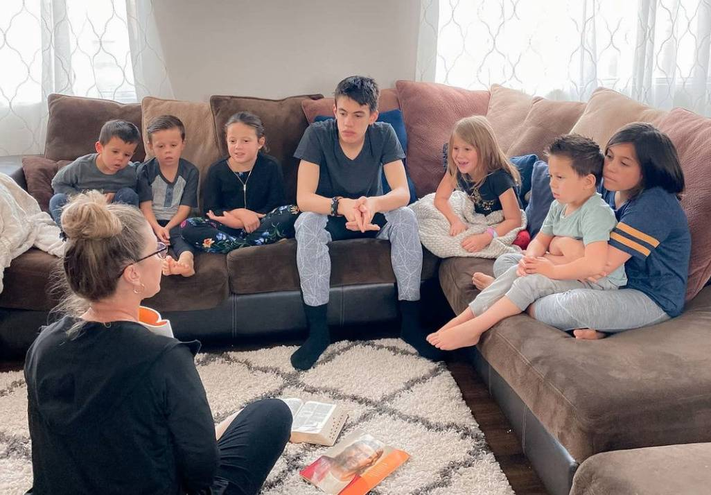 The seven kids sit and listen to Pam in their living room.