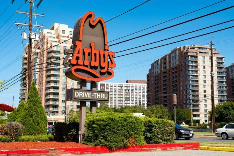 A sign for Arby's drive-thru is seen in front of skyscrapers.