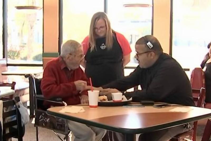 Two Arby's employees talk to Mr. Doug as he eats lunch.