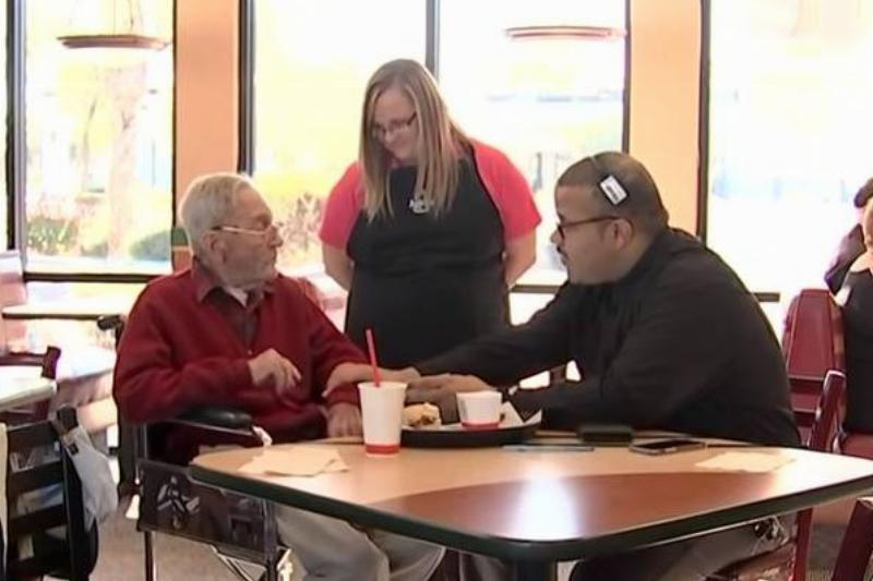 Two Arby's employees sit with Mr. Doug to give him a $200 gift card.