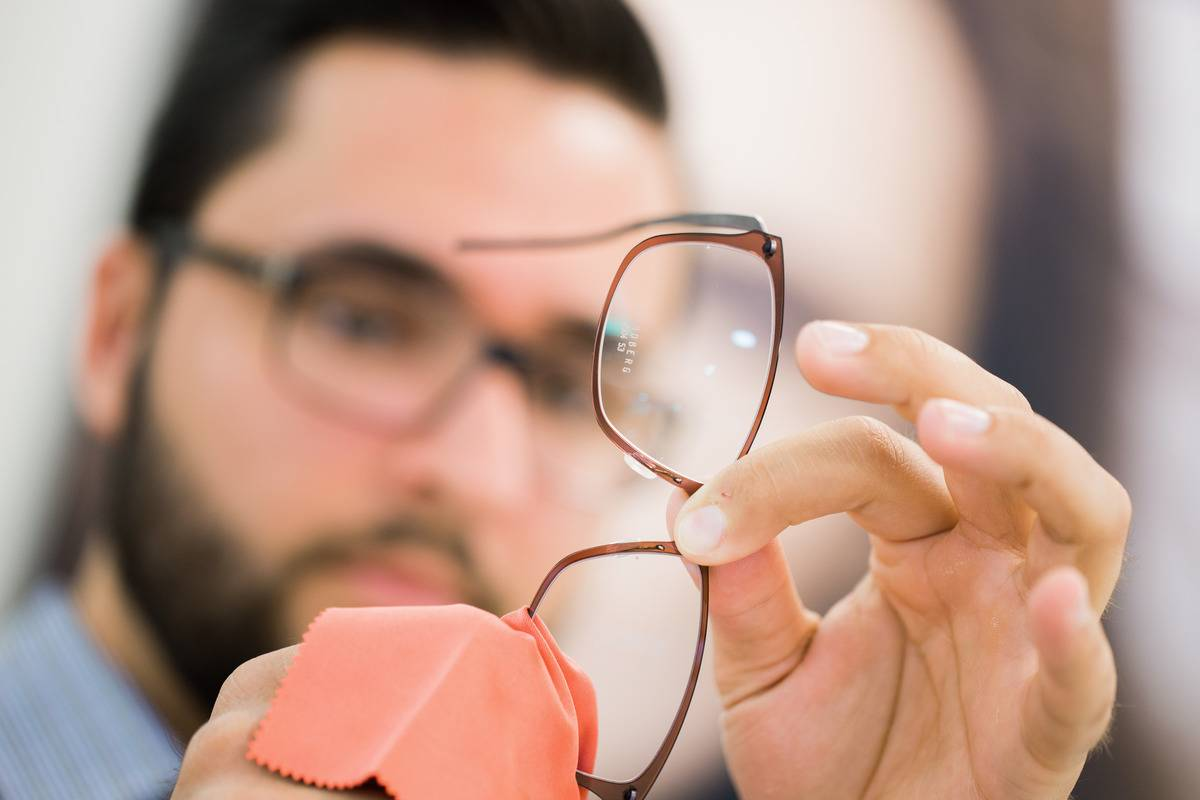 An optician cleans a pair of glasses.