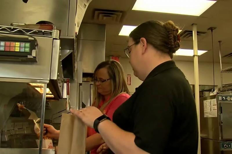 Gamage speaks to one of her coworkers while preparing food.