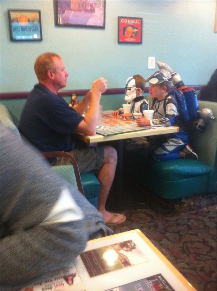 Dad eating at restaurant with his kids in star wars outfits