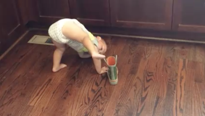 Silly baby tries to get books on in funny angles